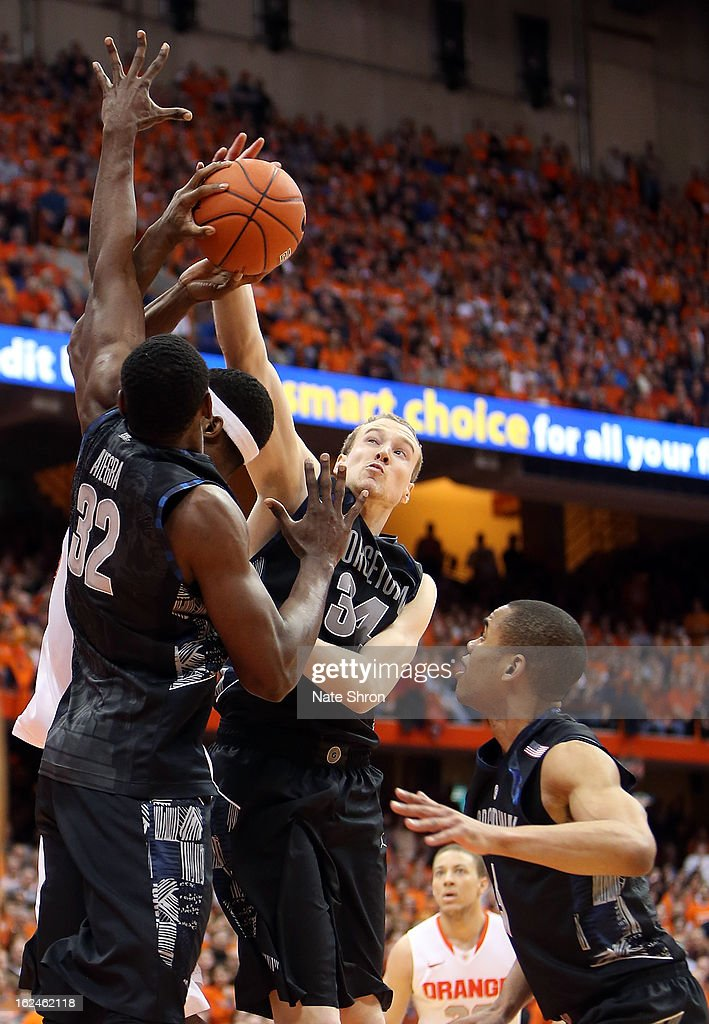 Nate Lubick #34 of the Georgetown Hoyas reaches for the rebound with the help of teamates Moses Ayegba #32 and Markel Starks #5 against C.J. Fair #5 of the Syracuse Orange during the game at the Carrier Dome on February 23, 2013 in Syracuse, New York.