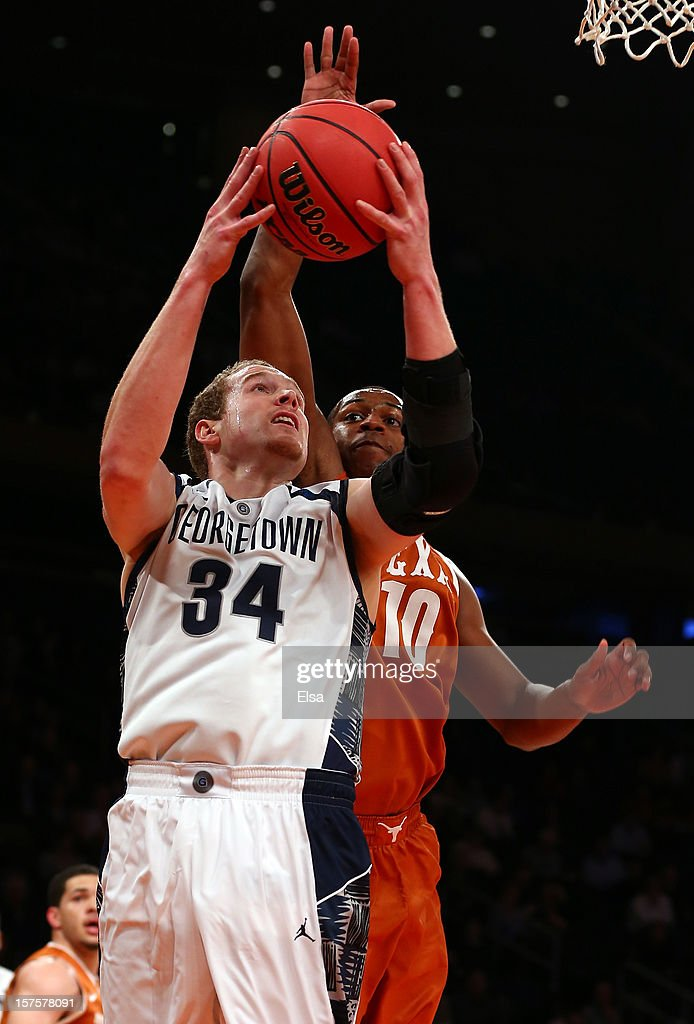 Nate Lubick #34 of the Georgetown Hoyas takes a shot as Jonathan Holmes #10 of the Texas Longhorns defends during the Jimmy V Classic on December 4, 2012 at Madison Square Garden in New York City.