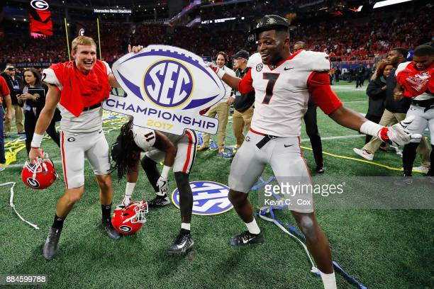 Nate McBride Keyon Brown and Lorenzo Carter of the Georgia Bulldogs celebrate beating the Auburn Tigers in the SEC Championship at MercedesBenz...