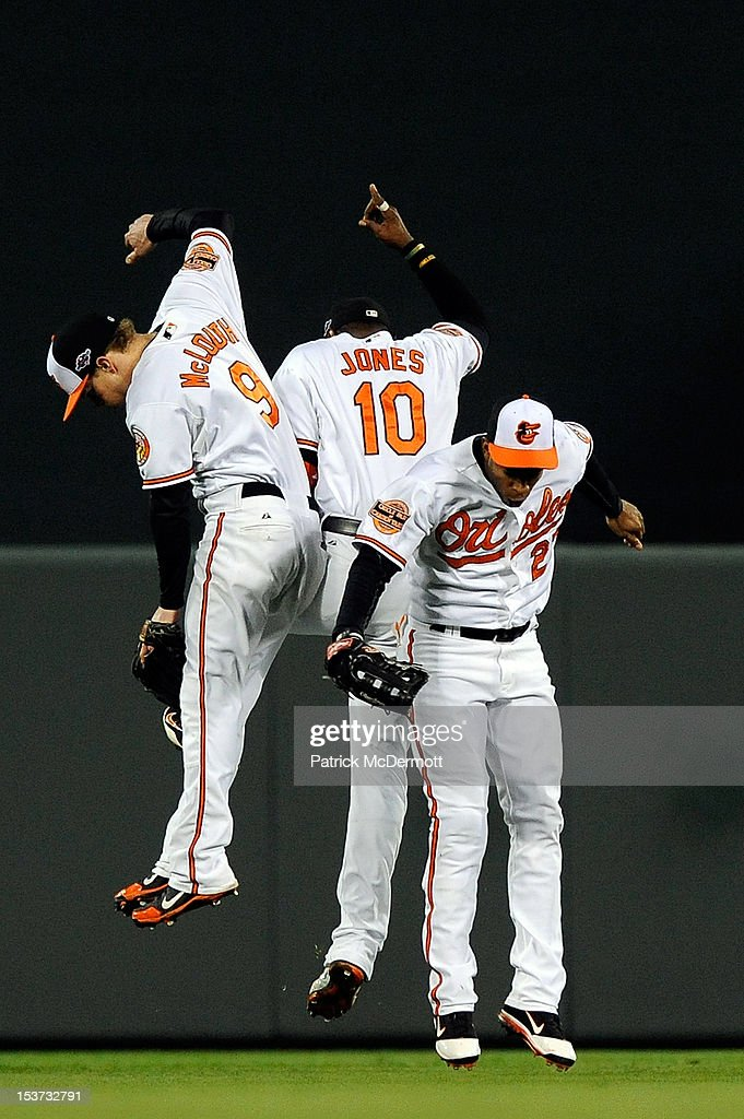 Nate McLouth #9, Adam Jones #10, and Endy Chavez #27 of the Baltimore Orioles celebrate after the Orioles defeated the New York Yankees 3-2 during Game Two of the American League Division Series at Oriole Park at Camden Yards on October 8, 2012 in Baltimore, Maryland.