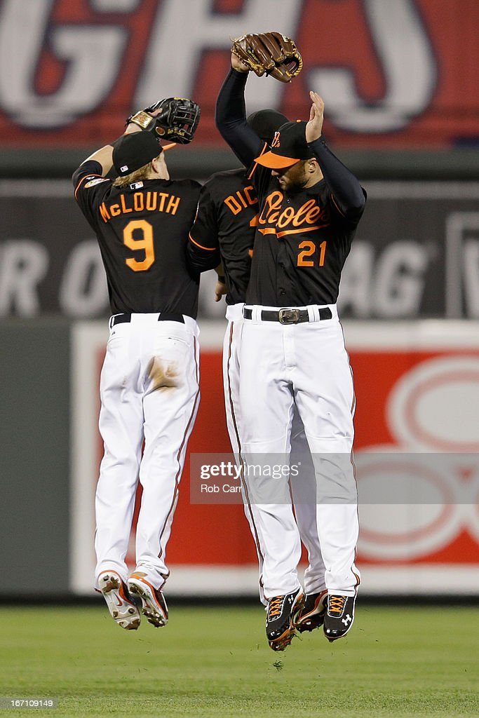 Nate McLouth #9, Chris Dickerson #36, and Nick Markakis #21 of the Baltimore Orioles celebrate in the outfiled following the Orioles 6-1 win over the Los Angeles Dodgers during game two of a double header at Oriole Park at Camden Yards on April 20, 2013 in Baltimore, Maryland.