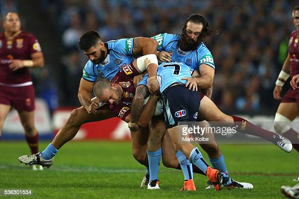 Nate Myles of the Maroons is tackled by James Tamou of the Blues Aaron Woods of the Blues and Adam Reynolds of the Blues during game one of the State...