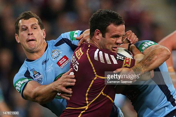 Nate Myles of the Maroons is tackled during game three of the 2012 State of Origin series between the Queensland Maroons and the New South Wales...