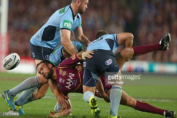 Nate Myles of the Maroons passes as he is tackled during game three of the ARL State of Origin series between the New South Wales Blues and the...