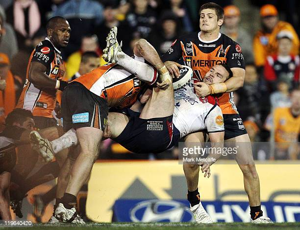 Nate Myles of the Roosters is tackled during the round 20 NRL match between the Wests Tigers and the Sydney Roosters at Leichhardt Oval on July 23...