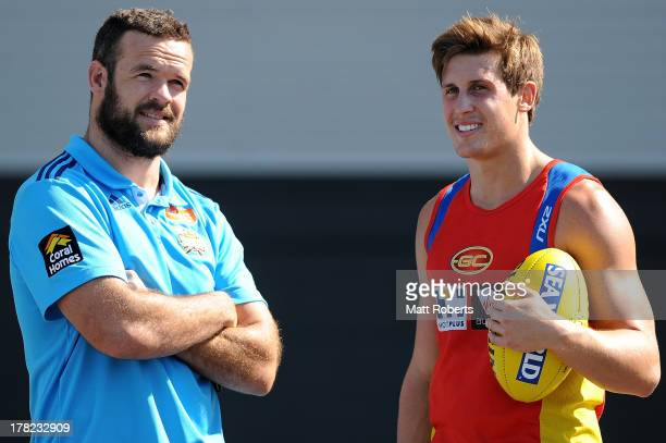 Nate Myles of the Titans speaks with David Swallow of the Suns after a Gold Coast Titans training session at Metricon Stadium on August 28 2013 on...