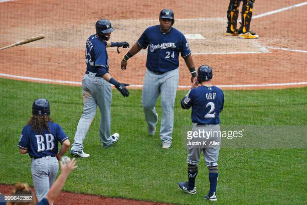 Nate Orf of the Milwaukee Brewers celebrates with Jesus Aguilar and Christian Yelich after scoring on a three RBI triple in the eighth inning against...