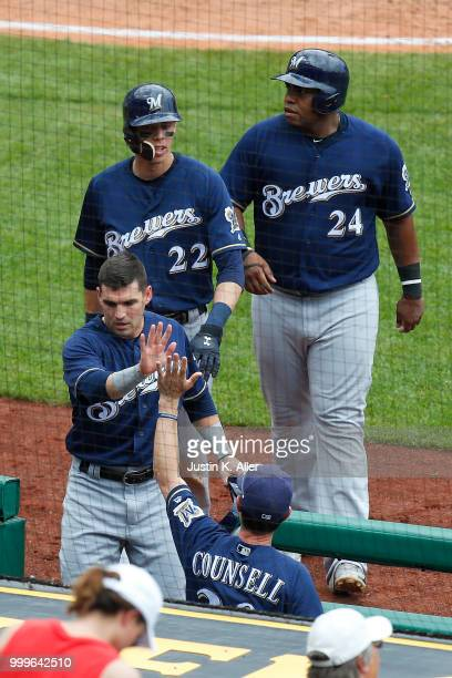 Nate Orf of the Milwaukee Brewers Jesus Aguilar and Christian Yelich celebrate with manager Craig Counsell of the Milwaukee Brewers after scoring on...
