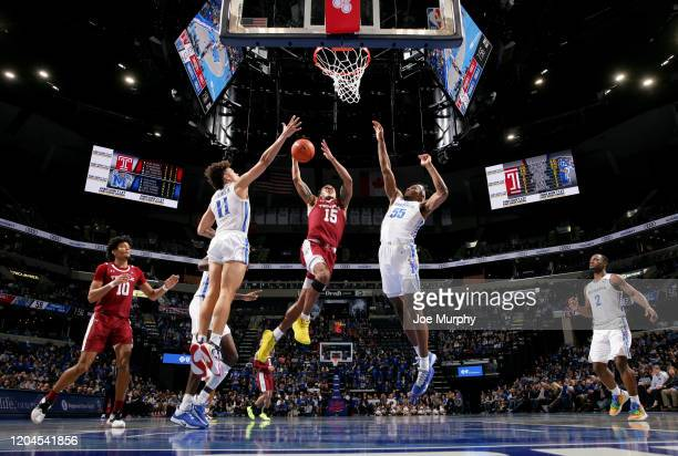 Nate Pierre-Louis of the Temple Owls drives to the basket against Lester Quinones and Precious Achiuwa of the Memphis Tigers during a game on...