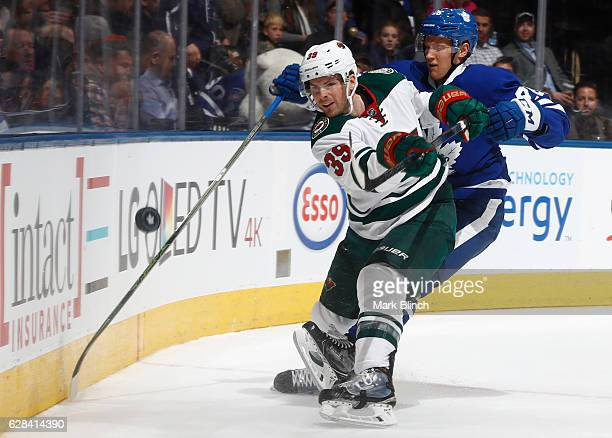 Nate Prosser of the Minnesota Wild and Nikita Soshnikov of the Toronto Maple Leafs battle for the puck during the third period at the Air Canada...