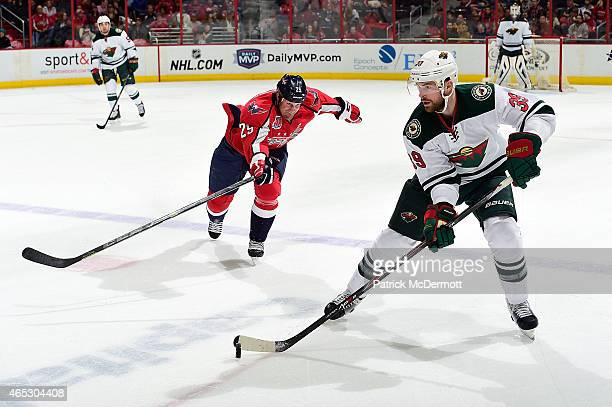 Nate Prosser of the Minnesota Wild controls the puck in the first period against Jason Chimera of the Washington Capitals during an NHL game on...