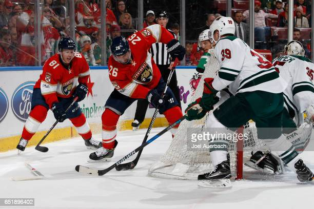 Nate Prosser of the Minnesota Wild defends the post as Thomas Vanek of the Florida Panthers attempts to pass the puck in front of the net during...