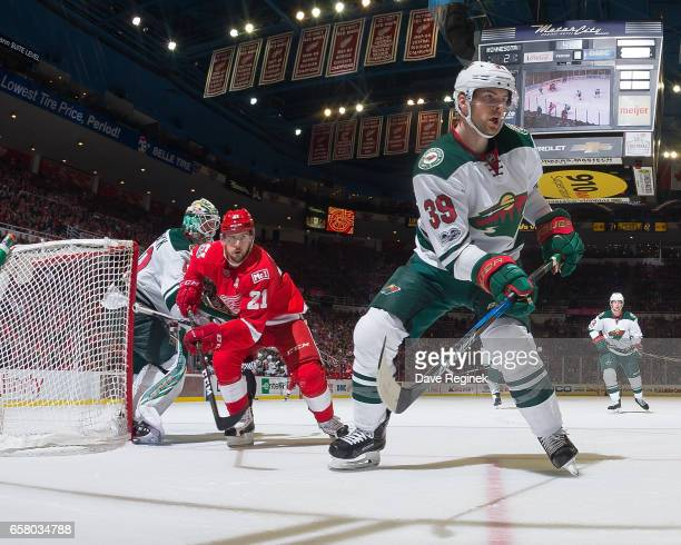 Nate Prosser of the Minnesota Wild follows the play in front of Tomas Tatar of the Detroit Red Wings as he screens goaltender Devan Dubnyk of the...