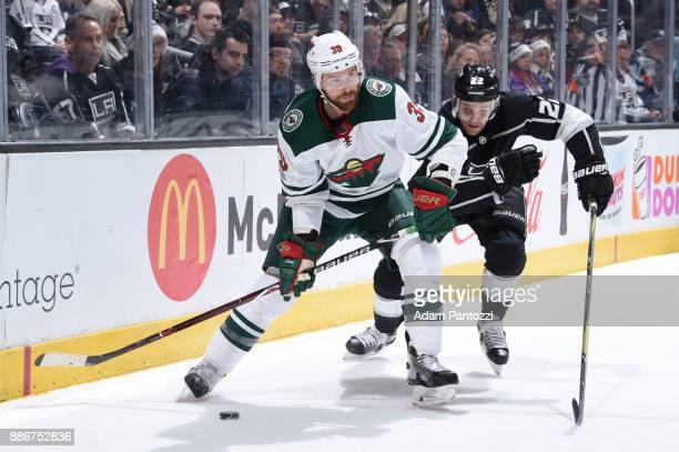 Nate Prosser of the Minnesota Wild handles the puck against Trevor Lewis of the Los Angeles Kings at STAPLES Center on December 5 2017 in Los Angeles...