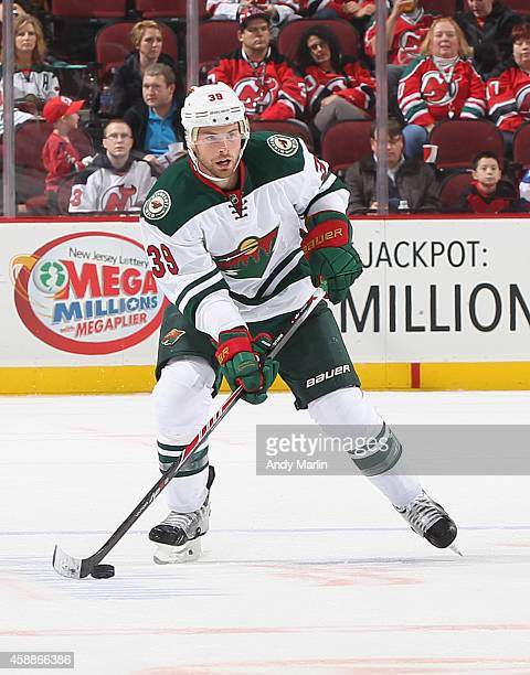 Nate Prosser of the Minnesota Wild plays the puck against the New Jersey Devils during the game at the Prudential Center on November 11 2014 in...