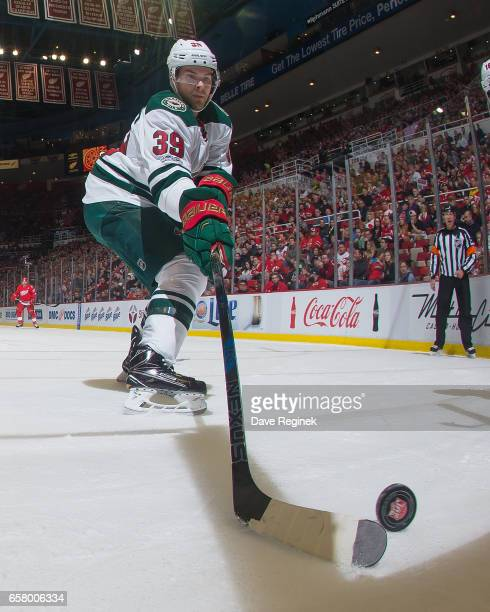 Nate Prosser of the Minnesota Wild reaches for the puck during an NHL game against the Detroit Red Wings at Joe Louis Arena on March 26 2017 in...