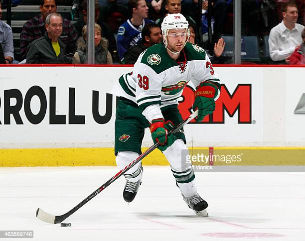 Nate Prosser of the Minnesota Wild skates up ice with the puck during their NHL game against the Vancouver Canucks at Rogers Arena February 16 2015...