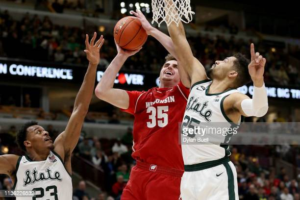 Nate Reuvers of the Wisconsin Badgers attempts a shot while being guarded by Xavier Tillman and Kenny Goins of the Michigan State Spartans in the...