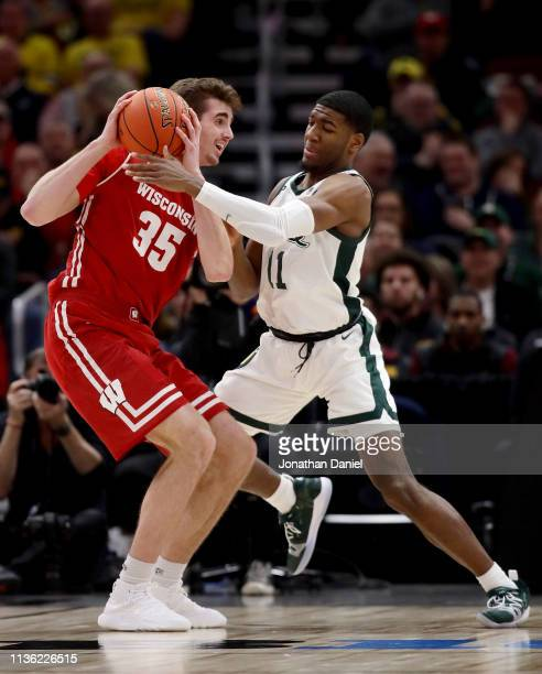 Nate Reuvers of the Wisconsin Badgers handles the ball while being guarded by Aaron Henry of the Michigan State Spartans in the second half during...