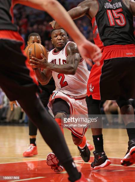 Nate Robinson of the Chicago Bulls drives into players for the Toronto Raptors including Amir Johnson at the United Center on April 9 2013 in Chicago...