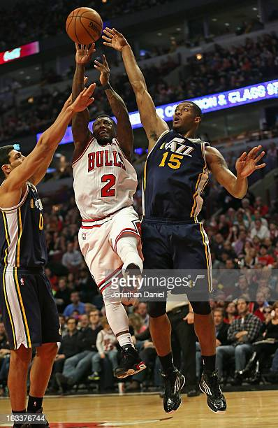 Nate Robinson of the Chicago Bulls goes up for a shot between Enes Kanter and Derrick Favors of the Utah Jazz at the United Center on March 8 2013 in...
