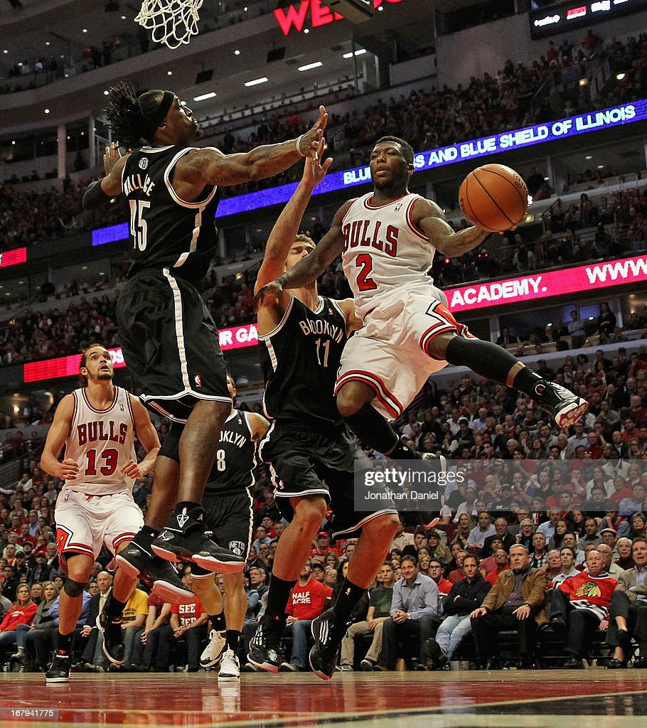 Nate Robinson #2 of the Chicago Bulls leaps to pass against Gerald Wallace #45 (L) and Brook Lopez #11 of the Brooklyn Nets in Game Six of the Eastern Conference Quarterfinals during the 2013 NBA Playoffs at the United Center on May 2, 2013 in Chicago, Illinois. The Nets defeated the Bulls 95-92.