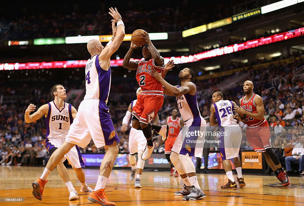 Nate Robinson #2 of the Chicago Bulls leaps to pass guarded by Marcin Gortat #4 and Markieff Morris #11 of the Phoenix Suns during the NBA game at US Airways Center on November 14, 2012 in Phoenix, Arizona. The Bulls defeated the Suns 112-106 in overtime.