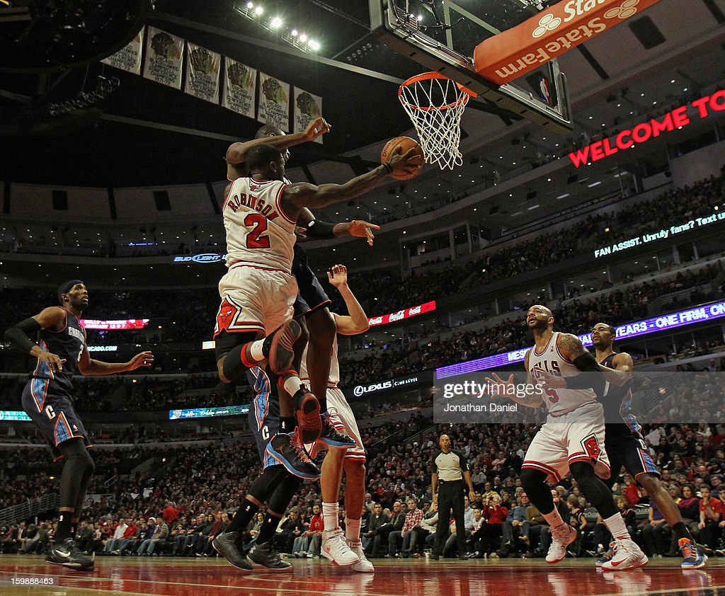 Nate Robinson #2 of the Chicago Bulls leaps to pass to teammate Carlos Boozer #5 against the Charlotte Bobcats at the United Center on December 31, 2012 in Chicago, Illinois. The Bobcats defeated the Bulls 91-81.