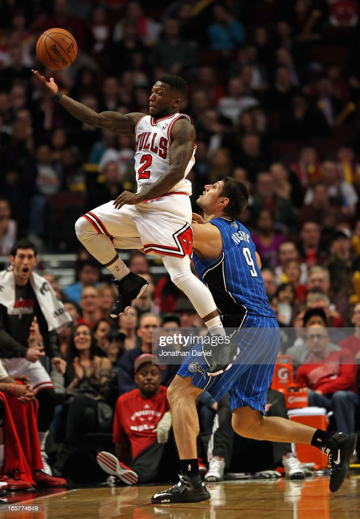Nate Robinson #2 of the Chicago Bulls leaps to save the ball from going out of bounds over Nikola Vucevic #9 of the Orlando Magic at the United Center on April 5, 2013 in Chicago, Illinois. The Bulls defeated the Magic 87-86.