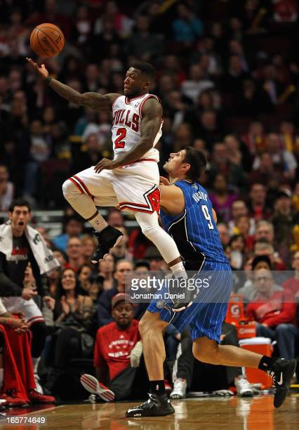 Nate Robinson of the Chicago Bulls leaps to save the ball from going out of bounds over Nikola Vucevic of the Orlando Magic at the United Center on...