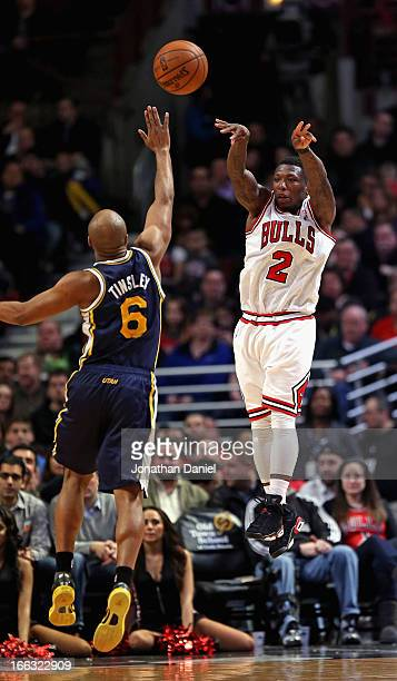 Nate Robinson of the Chicago Bulls passes over Jamaal Tinsley of the Utah Jazz at the United Center on March 8 2013 in Chicago Illinois The Bulls...