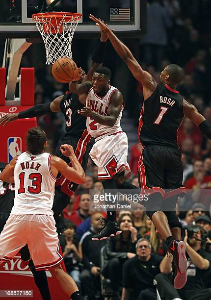 Nate Robinson of the Chicago Bulls passes to Joakim Noah between Dwyane Wade and Chris Bosh of the Miami Heat in Game Three of the Eastern Conference...