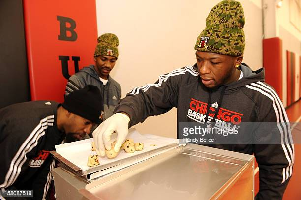 Nate Robinson of the Chicago Bulls prepares a tray of cookies for baking while team mates Richard Hamilton and Marquis Teague man the oven during the...