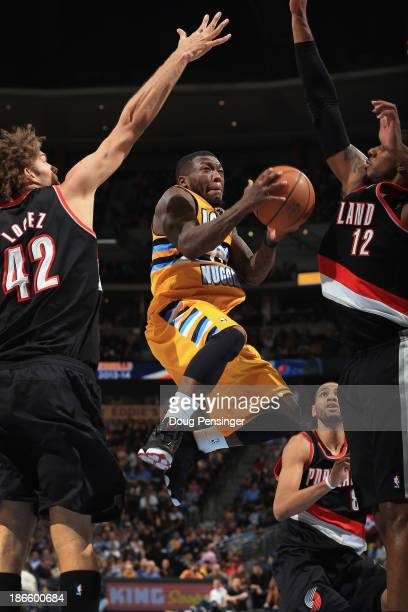 Nate Robinson of the Denver Nuggets lays up a shot between Robin Lopez and LaMarcus Aldridge of the Portland Trail Blazers at Pepsi Center on...