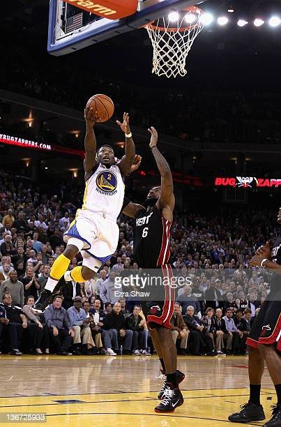 Nate Robinson of the Golden State Warriors drives on LeBron James of the Miami Heat at Oracle Arena on January 10 2012 in Oakland California NOTE TO...