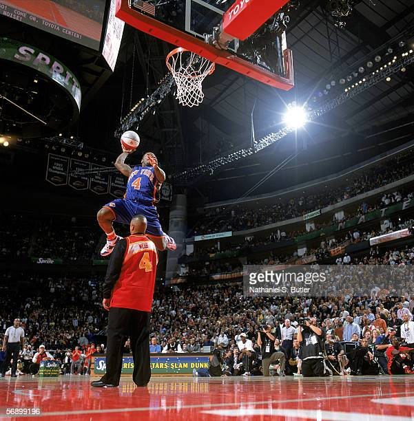 Nate Robinson of the New York Knicks completes a dunk as he jumps over former slam dunk champion Spud Webb during the Sprite Rising Stars Slam Dunk...