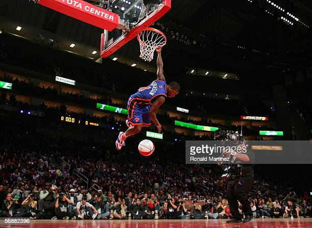 Nate Robinson of the New York Knicks hangs on the rim after making a dunk in the Sprite Rising Stars Slam Dunk competition during NBA AllStar Weekend...