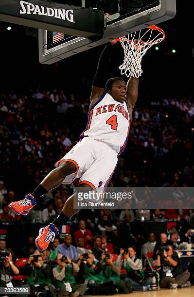 Nate Robinson of the New York Knicks hangs on the rim after missing a dunk in the final round of the Sprite Slam Dunk Competition during NBA All-Star...