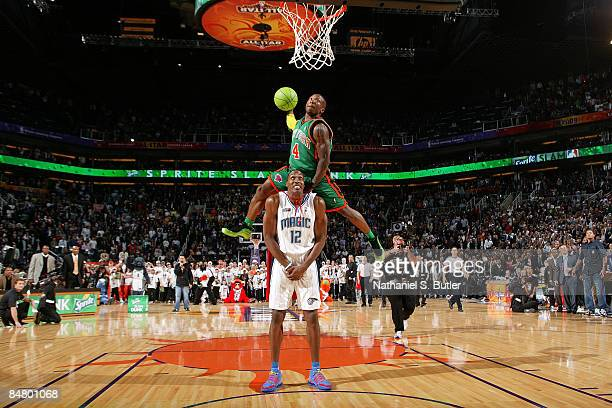 Nate Robinson of the New York Knicks jumps over Dwight Howard of the Orlando Magic on a dunk attempt during the Sprite Slam Dunk Contest on AllStar...