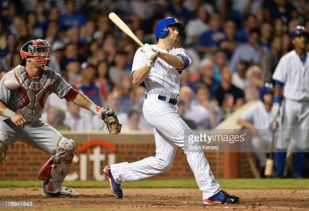 Nate Schierholtz of the Chicago Cubs follows through on a threerun home run scoring teammate Dioner Navarro as catcher Wilson Ramos of the Washington...