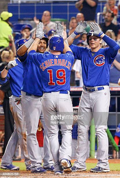 Nate Schierholtz of the Chicago Cubs high fives Ryan Sweeney and Starlin Castro after driving them in to score with a home run during the sixth...