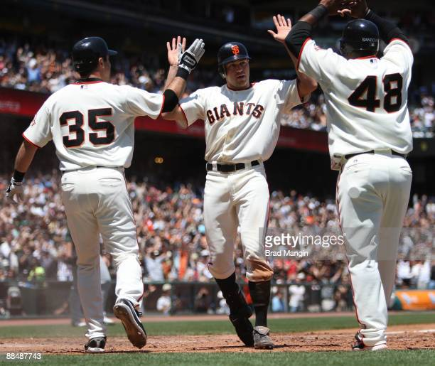 Nate Schierholtz of the San Francisco Giants is safe at home with an inside the park home run against the Oakland Athletics and celebrates with his...