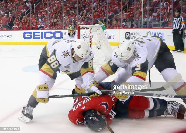 Nate Schmidt and Brayden McNabb of the Vegas Golden Knights combine to check Tom Wilson of the Washington Capitals during Game Three of the 2018 NHL...