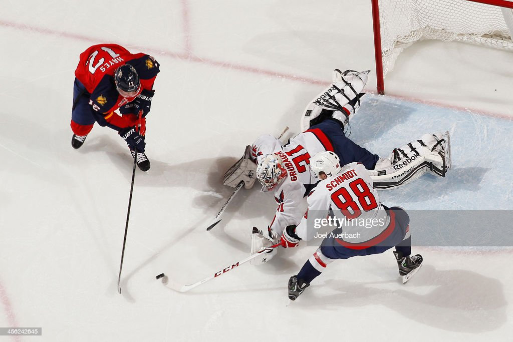 Nate Schmidt #88 assists goaltender Phillip Grubauer #31 of the Washington Capitals defend the net against a shot by Jimmy Hayes #12 of the Florida Panthers at the BB&T Center on December 13, 2013 in Sunrise, Florida. The Panthers defeated the Capitals 3-2 in a shootout.