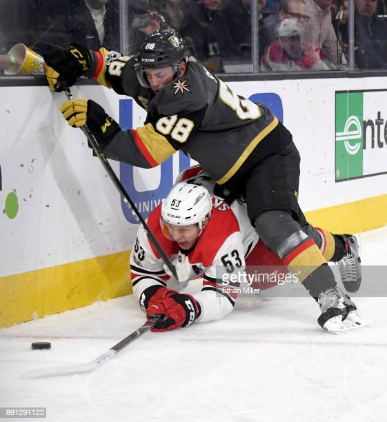 Nate Schmidt of the Vegas Golden Knights checks Jeff Skinner of the Carolina Hurricanes into the boards behind the net during the third period of...