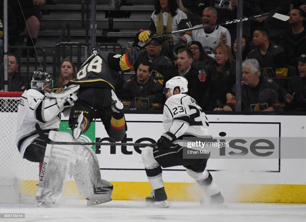 Nate Schmidt #88 of the Vegas Golden Knights crashes into Jack Campbell #1 of the Los Angeles Kings as Dustin Brown #23 of the Kings looks on in the first period of their game at T-Mobile Arena on February 27, 2018 in Las Vegas, Nevada. Schmidt recieved a two-minute minor penalty for interference on the play.