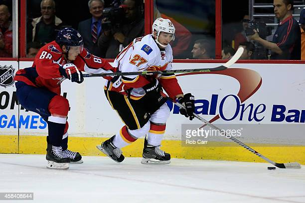 Nate Schmidt of the Washington Capitals and Sven Baertschi of the Calgary Flames go after the puck during the first period at Verizon Center on...