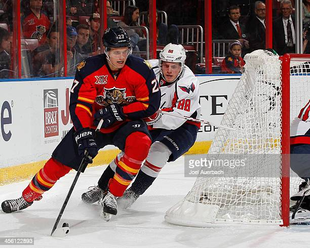 Nate Schmidt of the Washington Capitals defends against Nick Bjugstad of the Florida Panthers as he attempts to pass the puck in front of the net at...