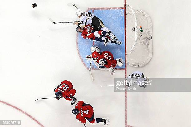 Nate Schmidt of the Washington Capitals is checked by Carl Hagelin of the Pittsburgh Penguins behind goalie Braden Holtby during the third period in...
