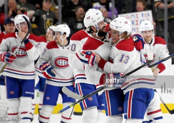 Nate Thompson and Max Domi of the Montreal Canadiens celebrate after Domi scored a goal in overtime to beat the Vegas Golden Knights 5-4 during their...
